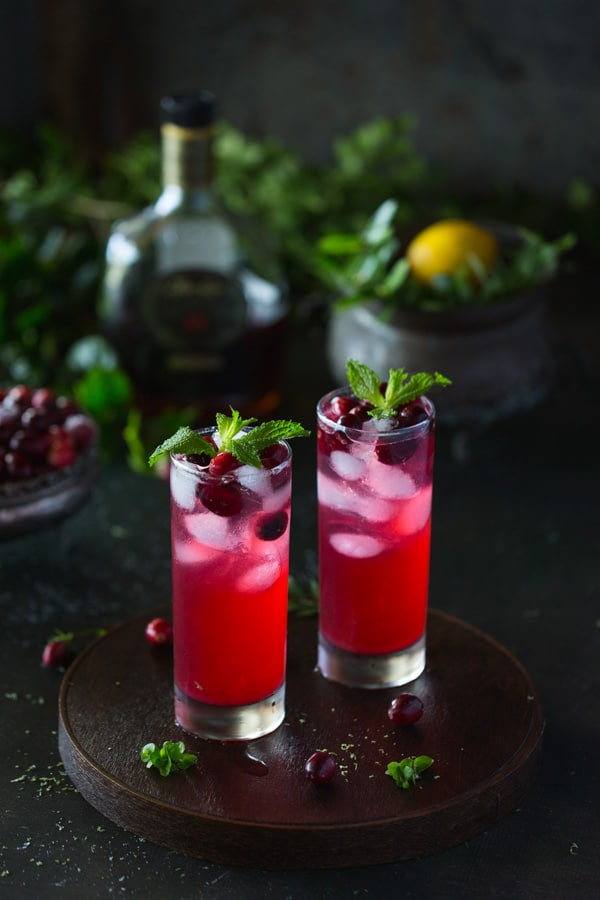 Two cranberry cocktails with a bottle of rum in the background