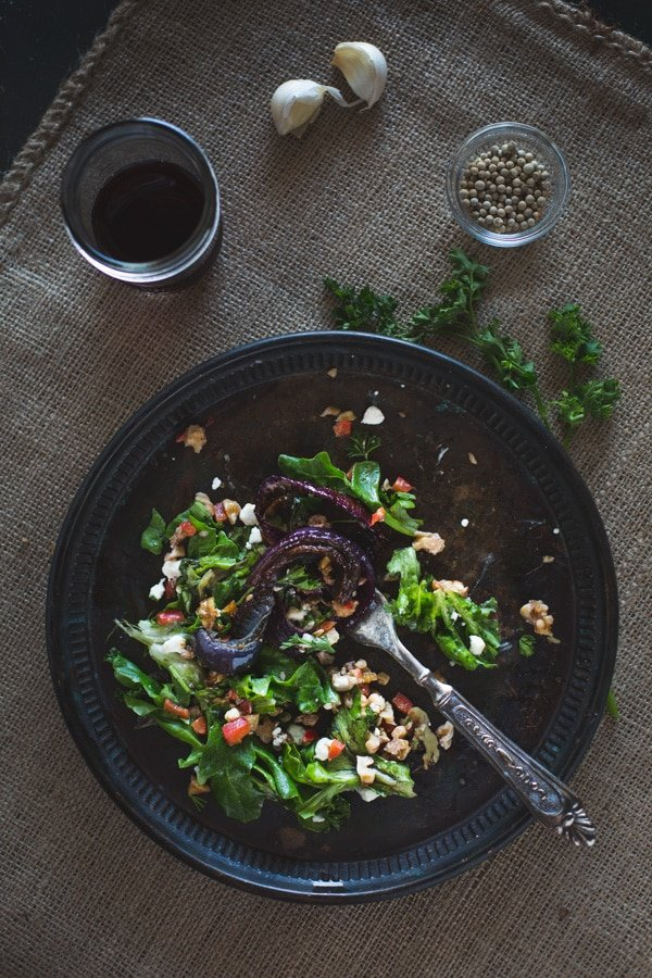 Overhead view of Roasted Red Onions with Walnut Salsa on a plate with a fork