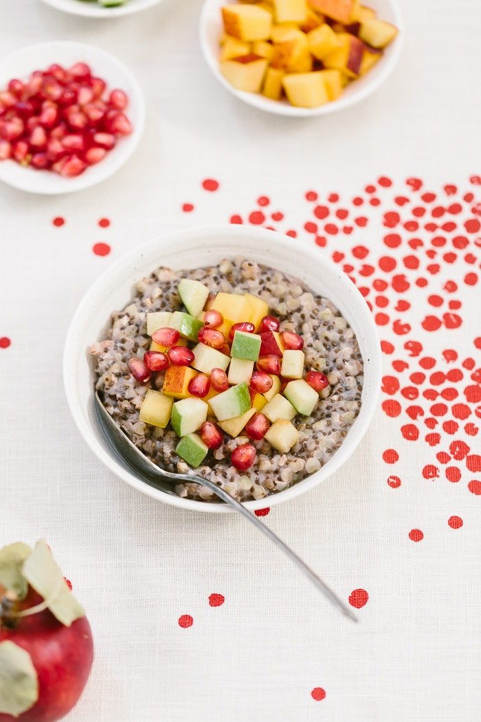 A bowl of overnight buckwheat groats are placed in a bowl and topped off with fruit