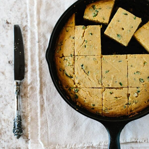 Jalapeño and Scallion Cornbread cut into squares in a skillet with a knife on the side