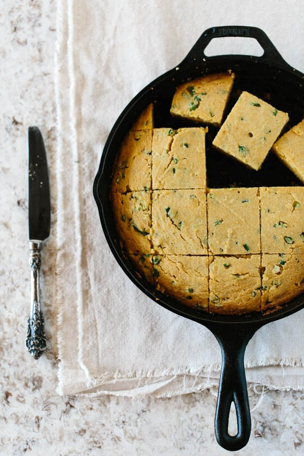 Jalapeno and Scallion Cornbread in a skillet cut into squares and a knife on the side