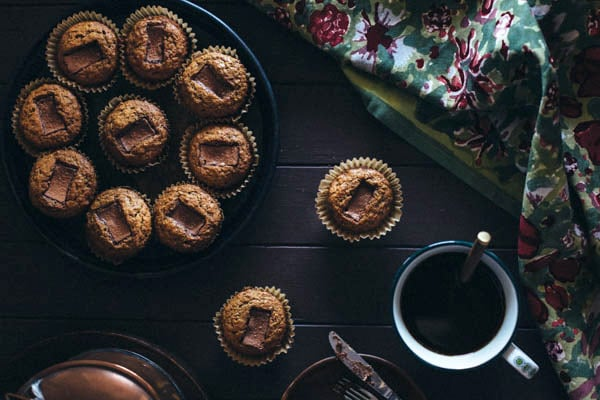 Several Banana Muffins with Toblerone Chunks with a cup of coffee