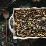 Oxtail Macaroni Gratin in a casserole dish with a wooden spoon on the side
