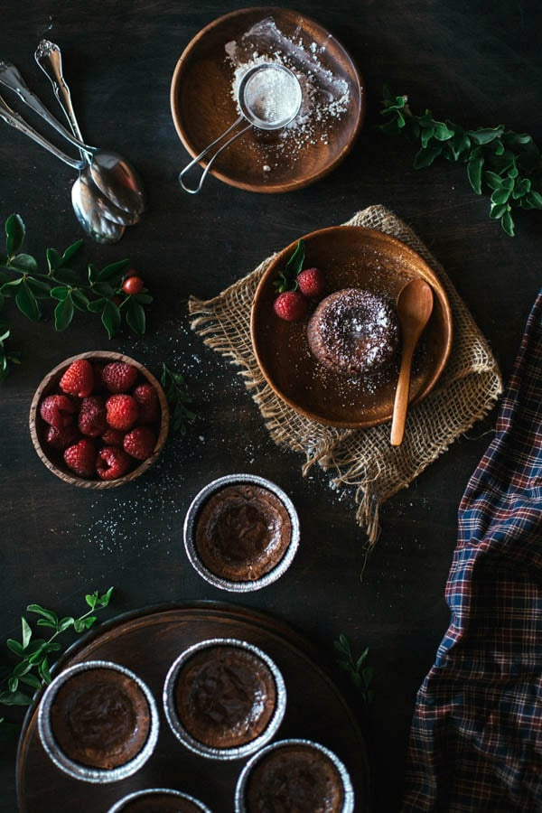 Overhead view of Chocolate Fondant with strawberries, flatware and garnishes on the side