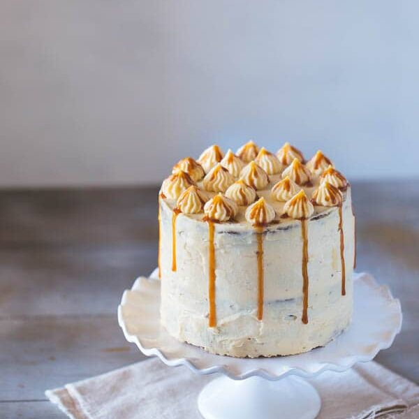 Banana Cake with Caramel Frosting on a cake stand from the front view