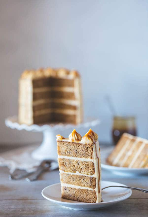 A slice of Banana Cake with Caramel Frosting with slices in the background
