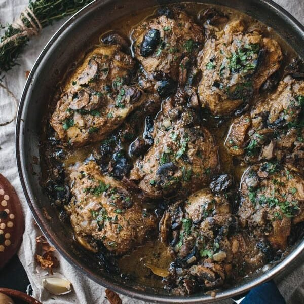 Braised Chicken Thighs with Mushrooms and Almond Purée in a pan