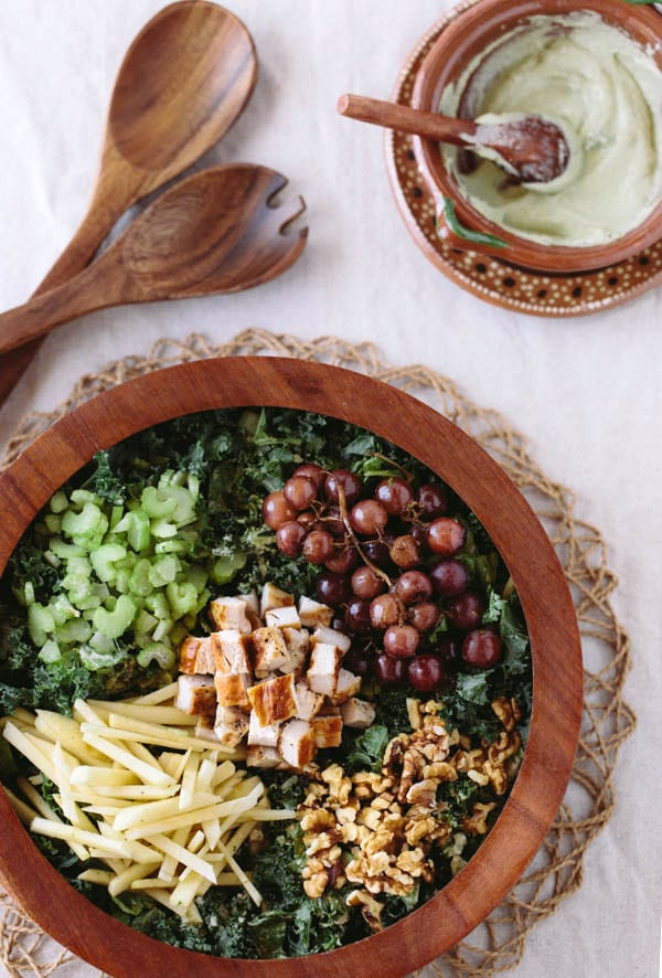 "Kale Waldorf Chicken Salad with Cashew and Avocado ""Mayo"" in a decorative bowl and wooden spoons"