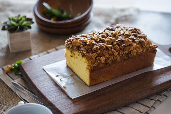 Sliced Orange Polenta Cake with Almond and Oat Streusel on a cutting board