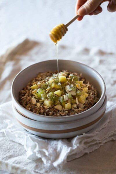 A bowl of Almond-Kasha Porridge with Ginger and Pineapple with honey being drizzled