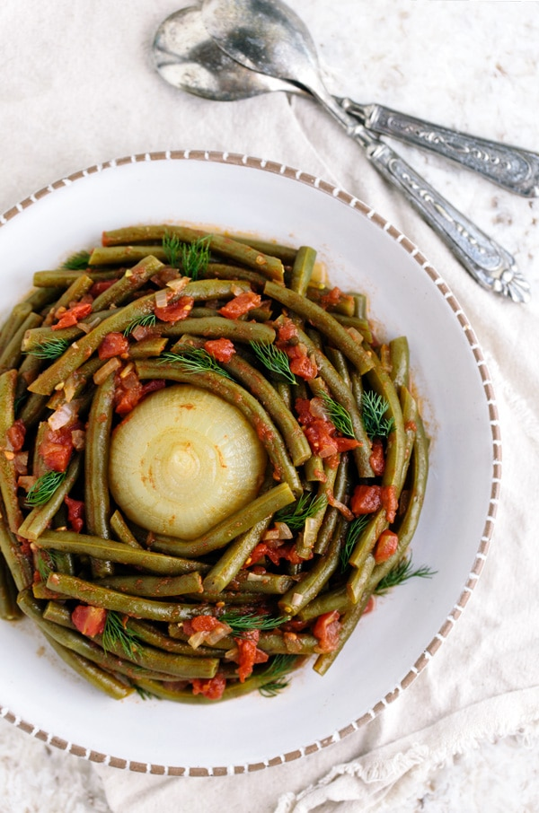 Mediterranean Style Green Beans recipe served with a cooked onion in the middle