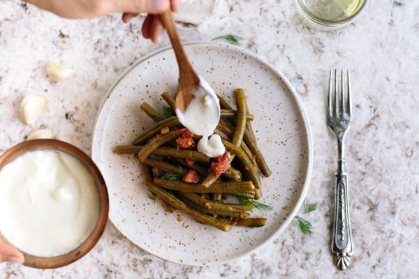 Easy green bean salad is being drizzled with yogurt dressing