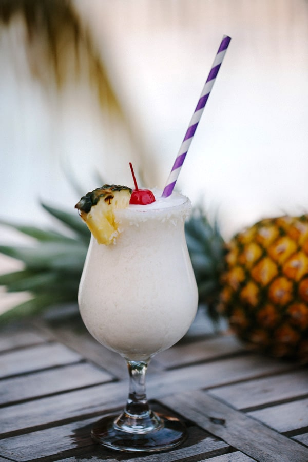 Side view of a Virgin Gorda Style Pina Colada with a pineapple in the background