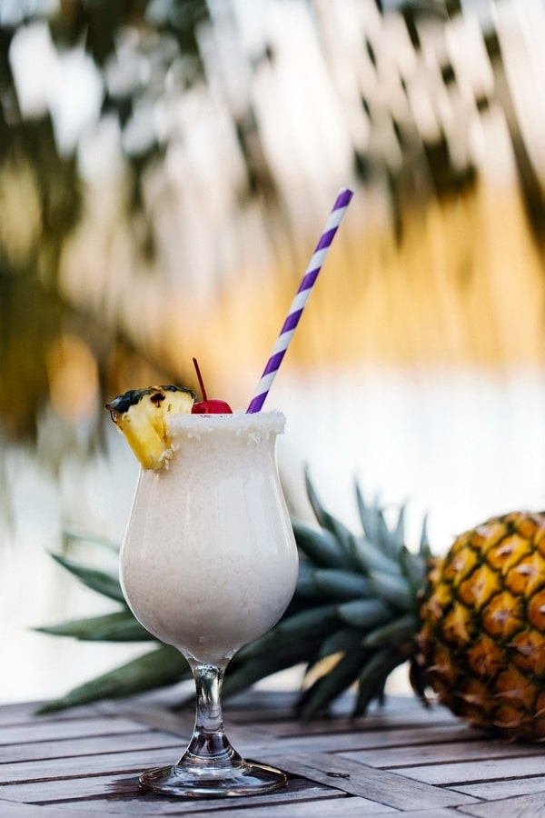 Glass of Pina Colada with a pineapple in the background