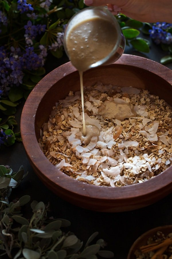 Bowl of granola with coconut flakes being drizzled with almond milk mixture