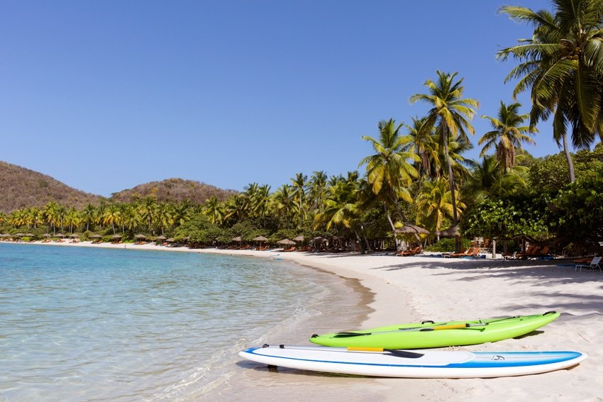 Two kayaks on a beach with lounge chairs and palm trees in the background