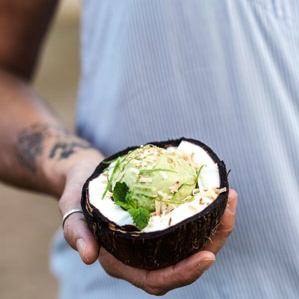 Avocado Coconut Ice Cream placed in a coconut bowl in a woman's hand
