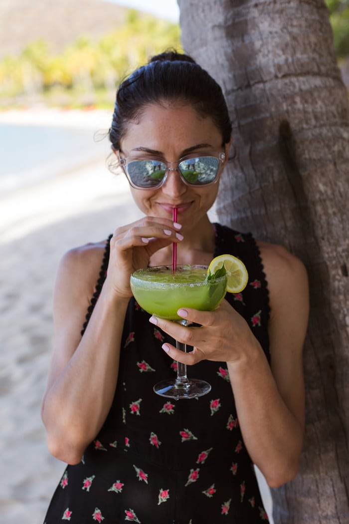 A woman standing next to a tree holding a Basil Margarita