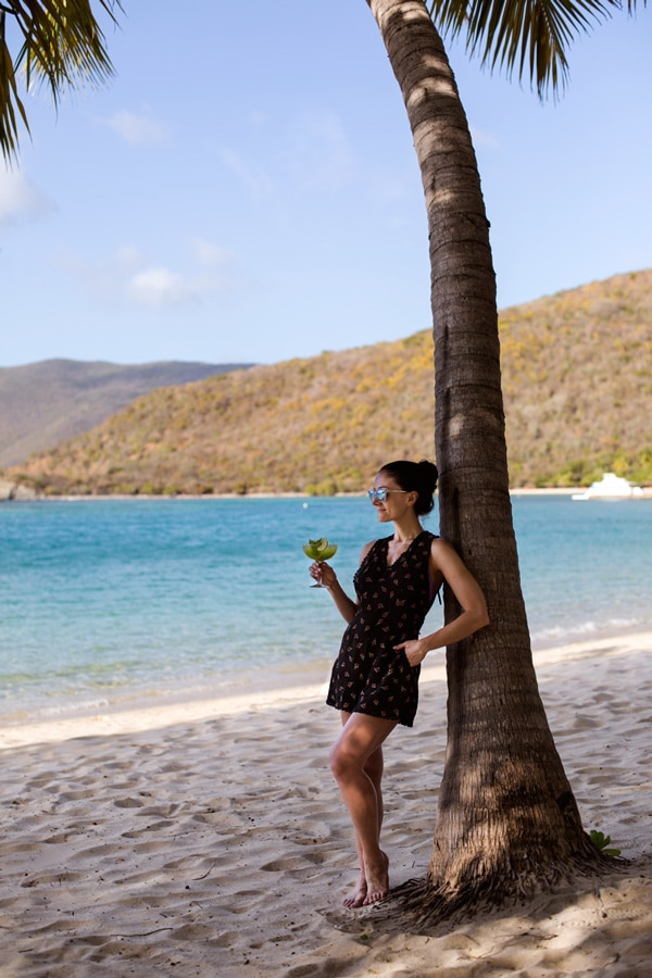 A woman on the beach holding a Margarita standing next to a tree