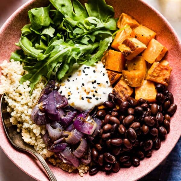 sweet potato quinoa bowl with black beans and tahini dressing placed in a bowl