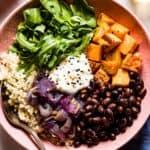 Sweet potato quinoa bowl garnished with tahini dressing and arugula