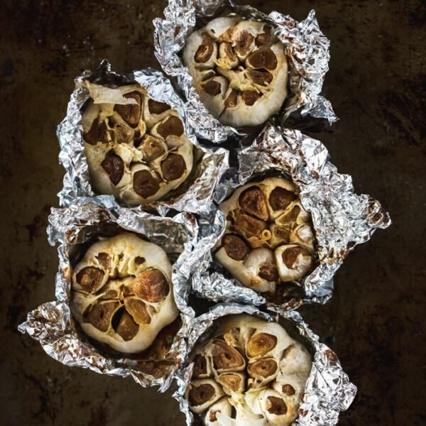 5 Oven-Roasted Garlic buds semi wrapped in aluminum foil