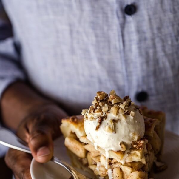 Person holding a slice of Caramel Apple Pie with a scoop of ice cream