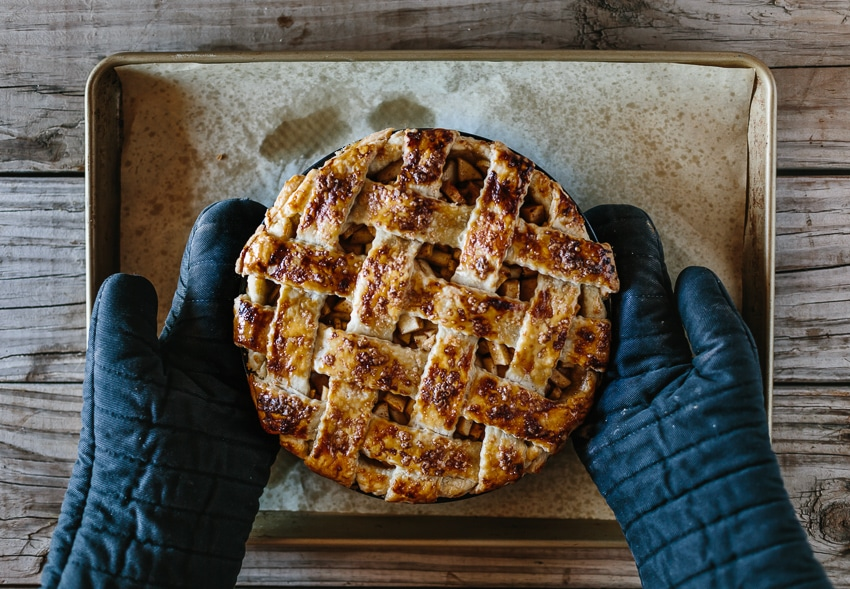 Person removing an Apple Pie using a oven mitts