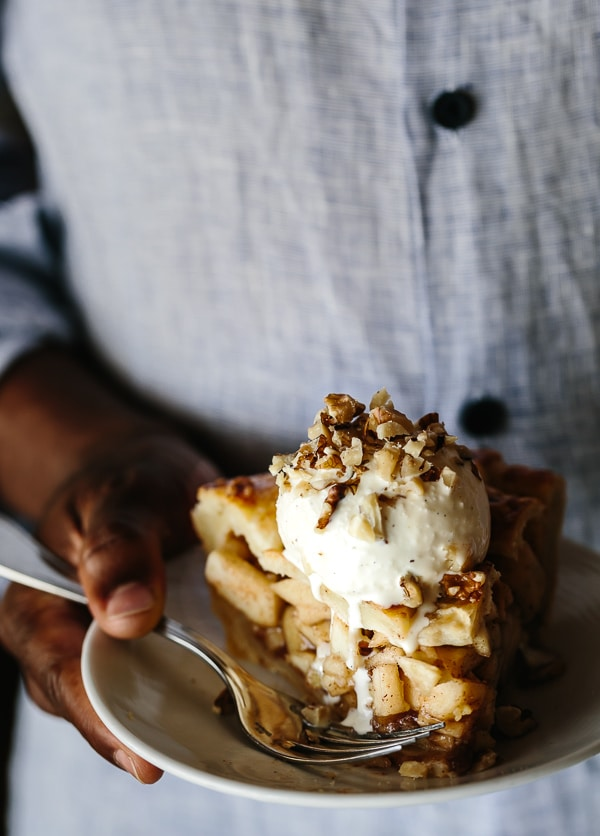 Person holding a slice Caramel Apple Pie with a scoop of ice cream on a small plate