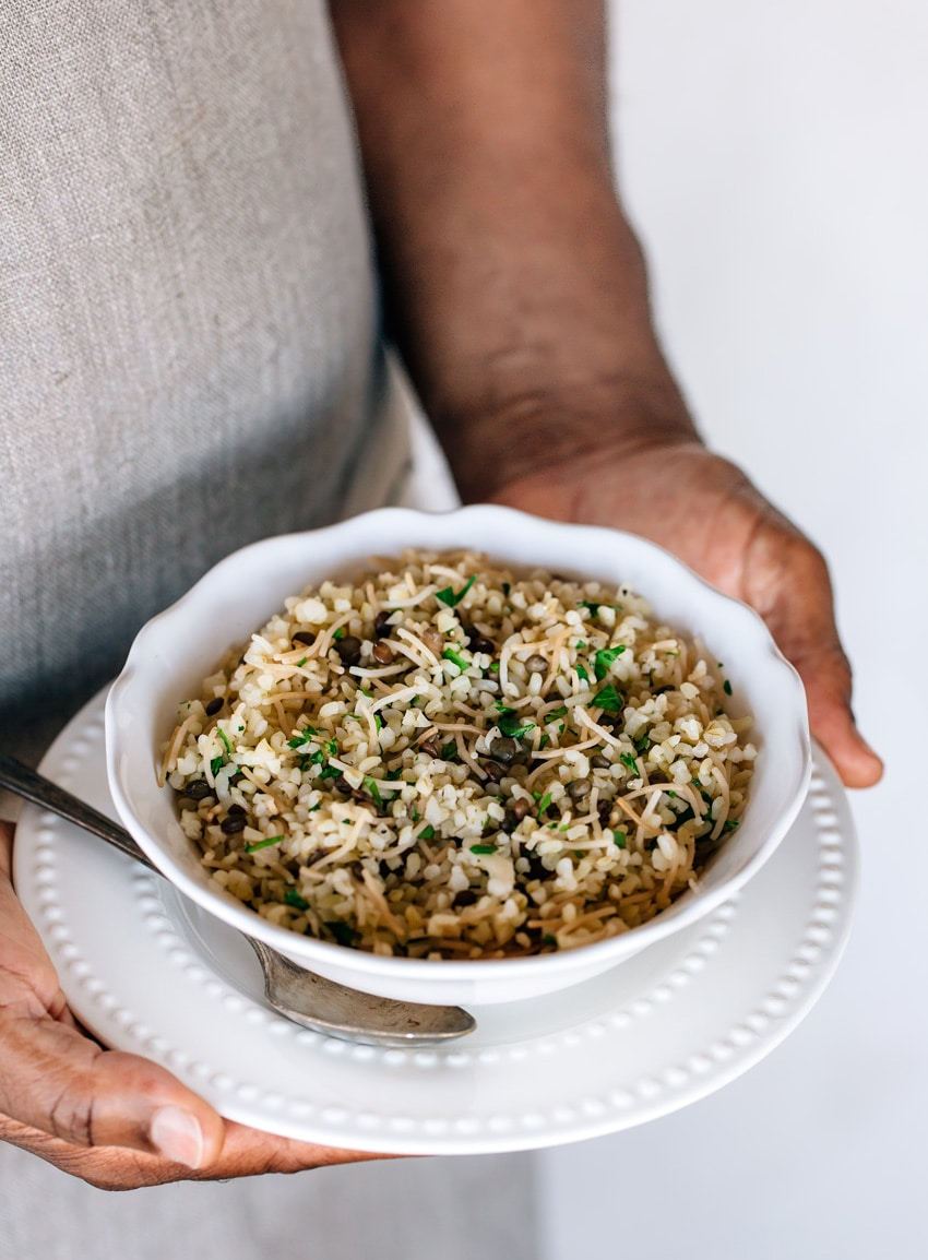 A bowl of Turkish bulgur pilaf photographed in the hands of a person from the side view.