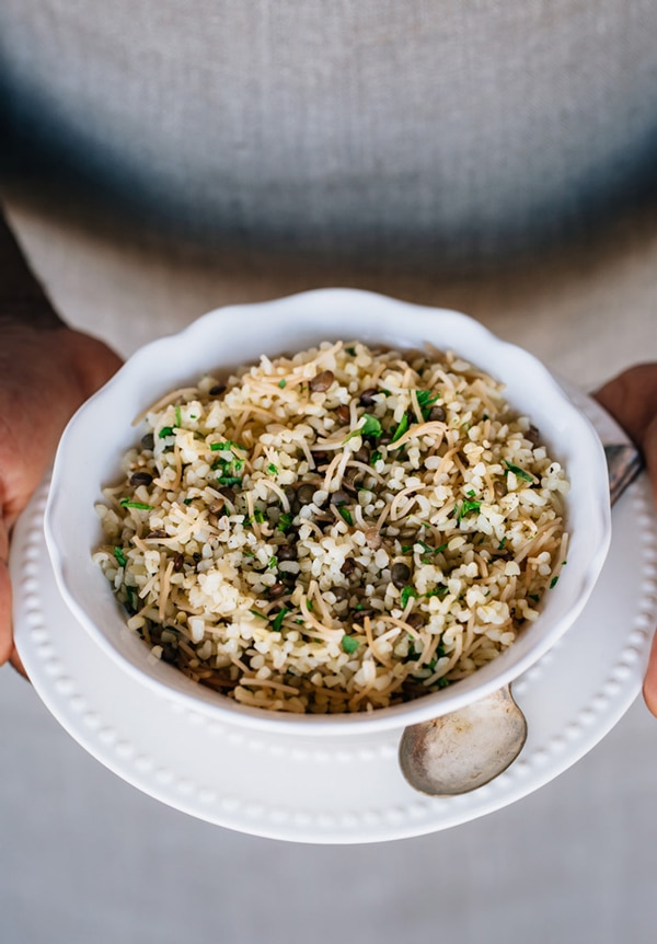 A bowl of bulgur pilaf with vermicelli is photographed in the hands of a person from the front view.