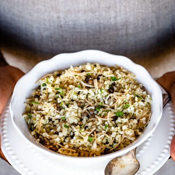 A bowl of bulgur pilaf is photographed from the front view in the hands of a man.