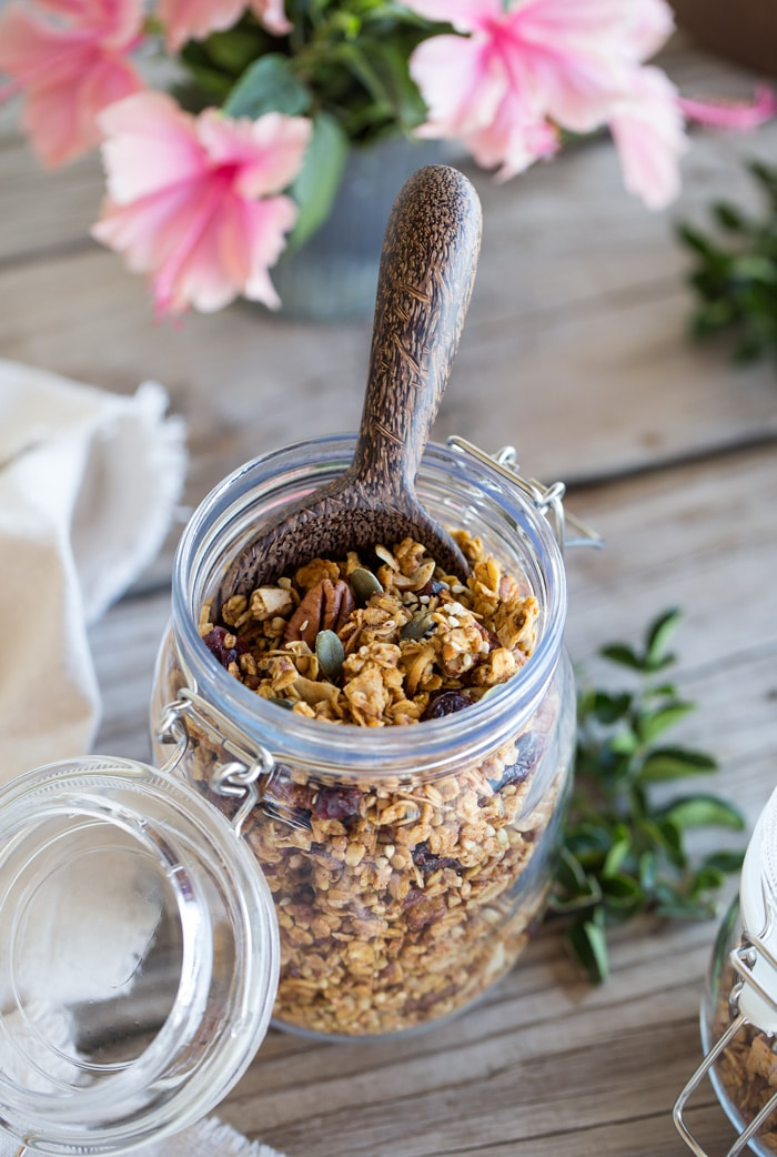 Jar of Spicy Pumpkin, Maple, and Tahini Granola with a wooden spoon