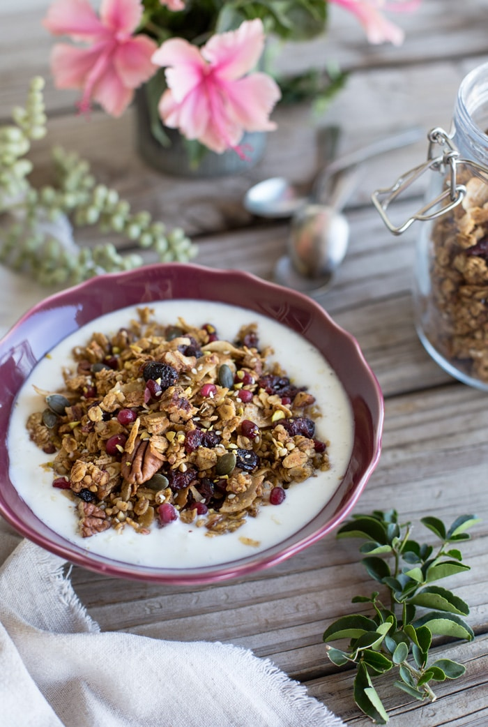 A bowl of Tahini Granola with milk with leaves on the side