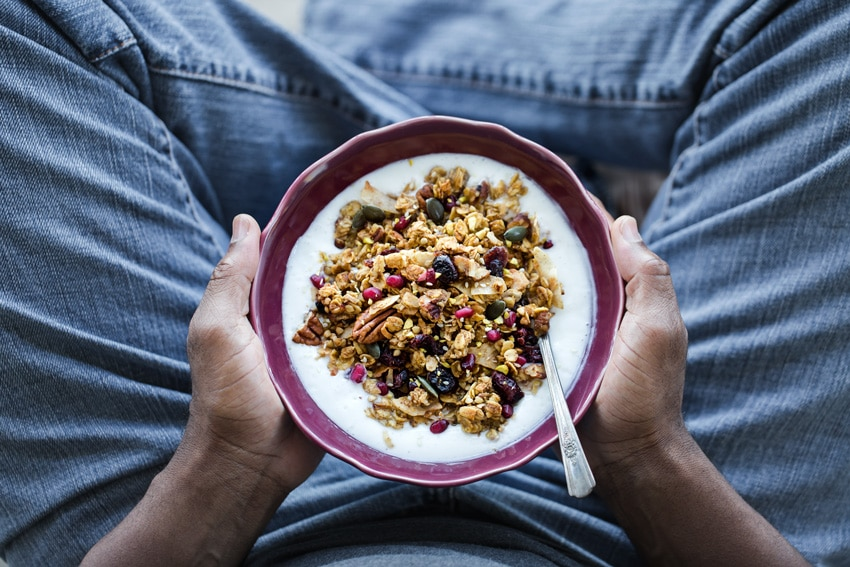 Person holding a bowl of Spicy Pumpkin, Maple, and Tahini Granola with milk