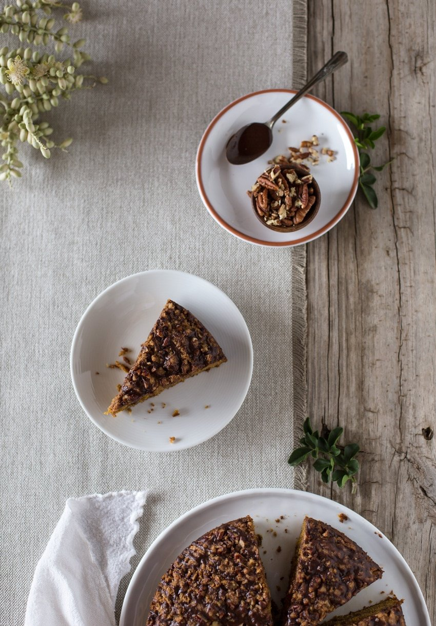 A slice of Pumpkin Coffee Cake on a plate with a bowl of nuts and spoon on a napkin with a flower