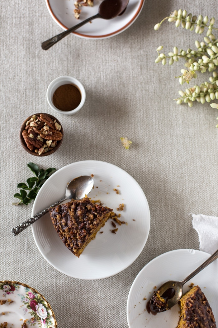 Two separate slices of Pumpkin Coffee Cake with Cocoa Vanilla Glaze on a plate with a cup of coffee, cup of nuts and flower on a napkin