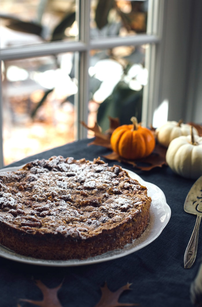 Pumpkin Pie Crumble cake on a plate with 3 miniature pumpkins in the background
