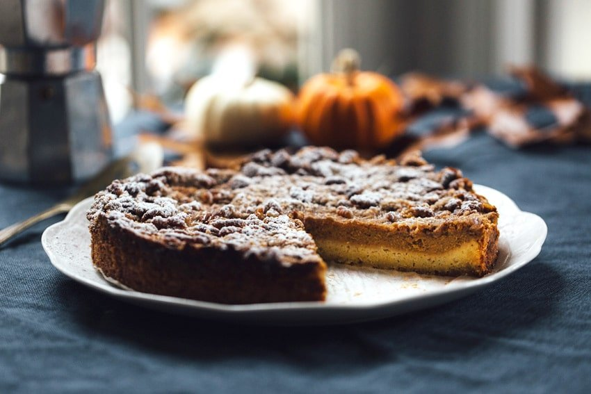 Whole Pumpkin Pie Crumble cake with one slice missing and miniature pumpkins in the background