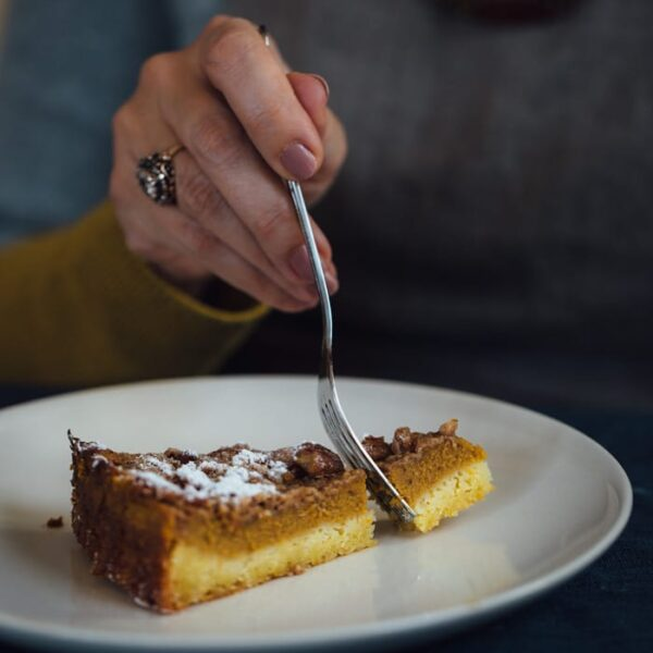 Person holding a slice of Pumpkin Pie Crumble on a plate with a fork cutting the pumpkin crumble