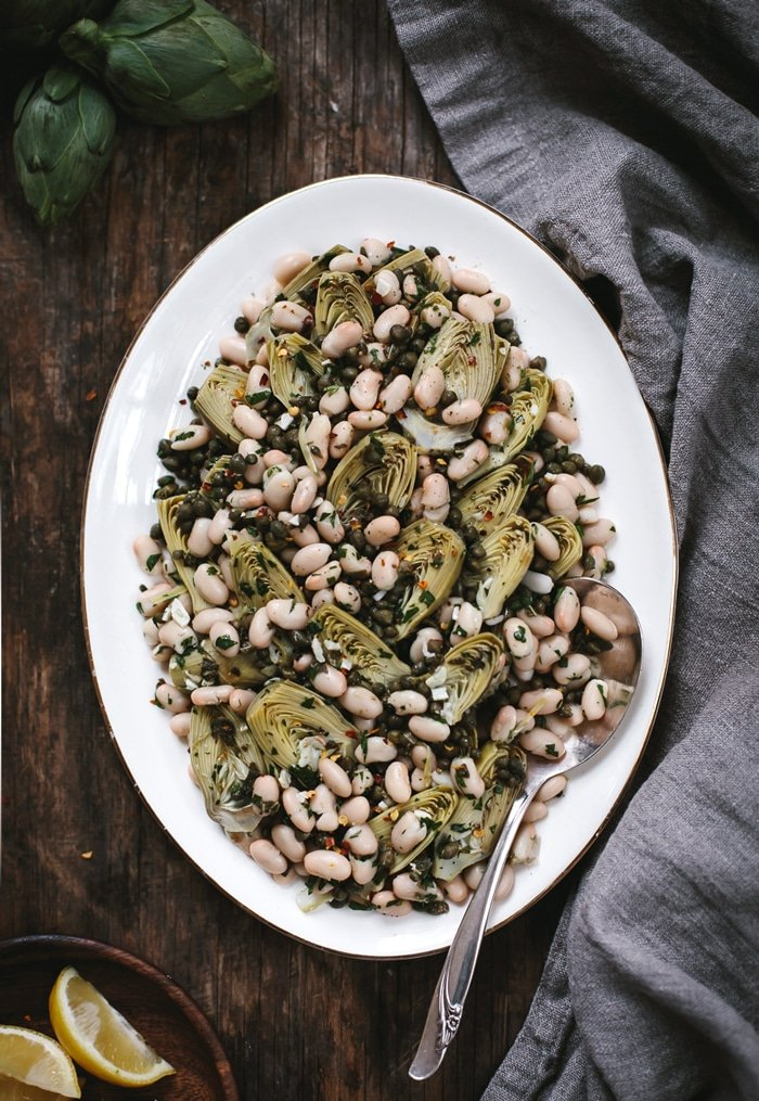 Overhead view of a Warm Braised Baby Artichoke Salad with White Beans and Manchego on a platter with a spoon