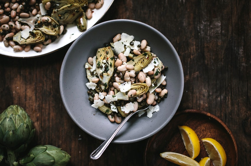 Bowl of Baby Artichoke Salad with White Beans and Manchego with lemons and artichokes on the side