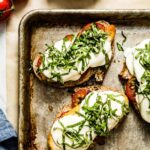 Caprese Chicken Sandwich on a sheet pan garnished with basil