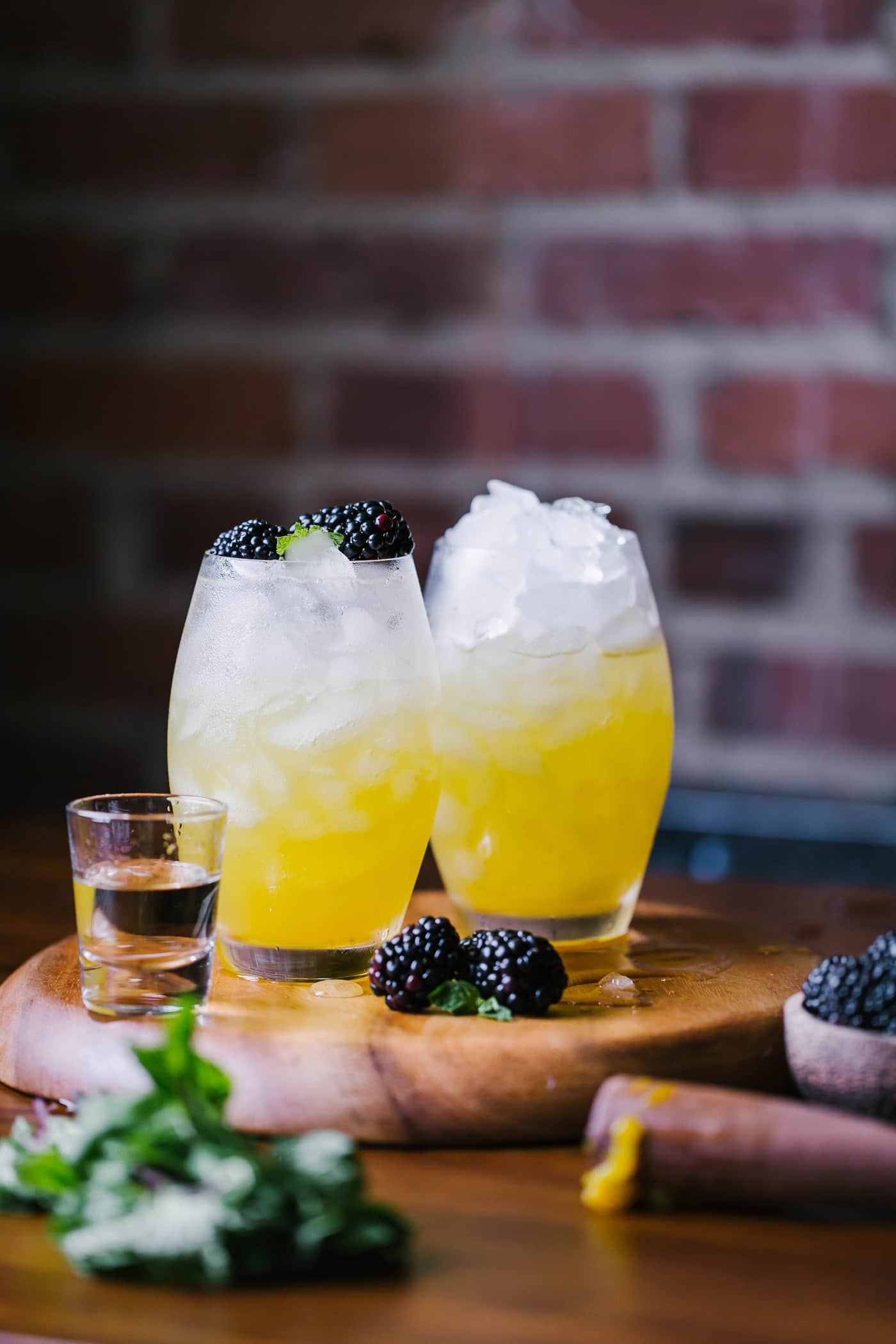 Two glass of mango and blackberry vodka cooler garnished with fresh blackberries photographed side by side  from the front view.