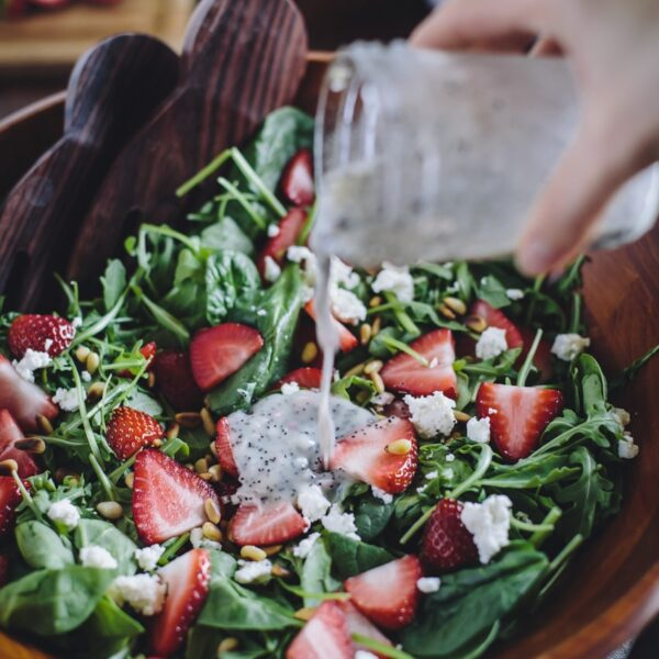 Strawberry, Spinach, and Arugula Salad with Lighter Poppy Seed Dressing being poured