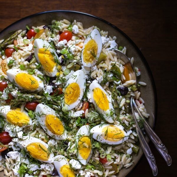 Mediterranean-Style Orzo Salad with Spring Vegetables in a bowl with flatware on the side