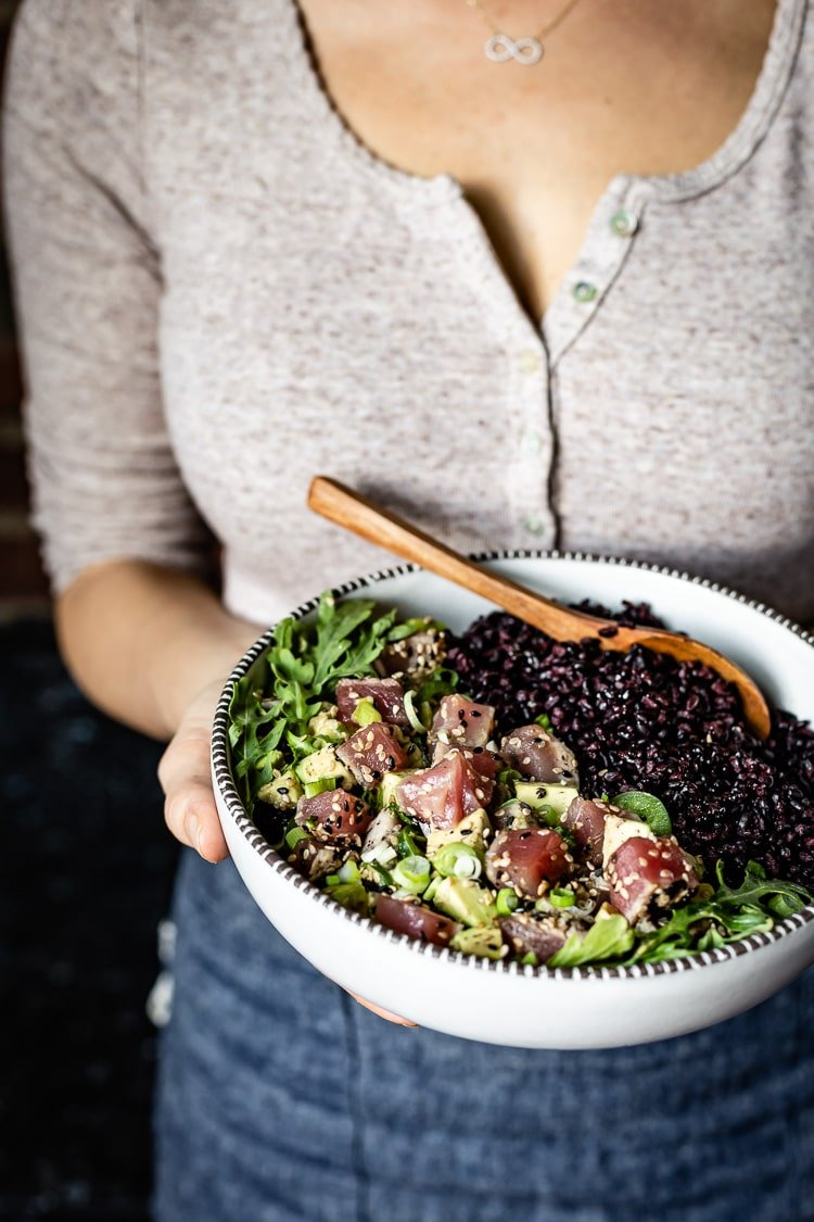 a woman is serving a bowl black Rice Recipe topped off with tuna