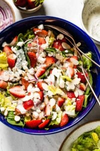Strawberry Spinach Salad with Poppy seed dressing in a bowl with two spoons on the side