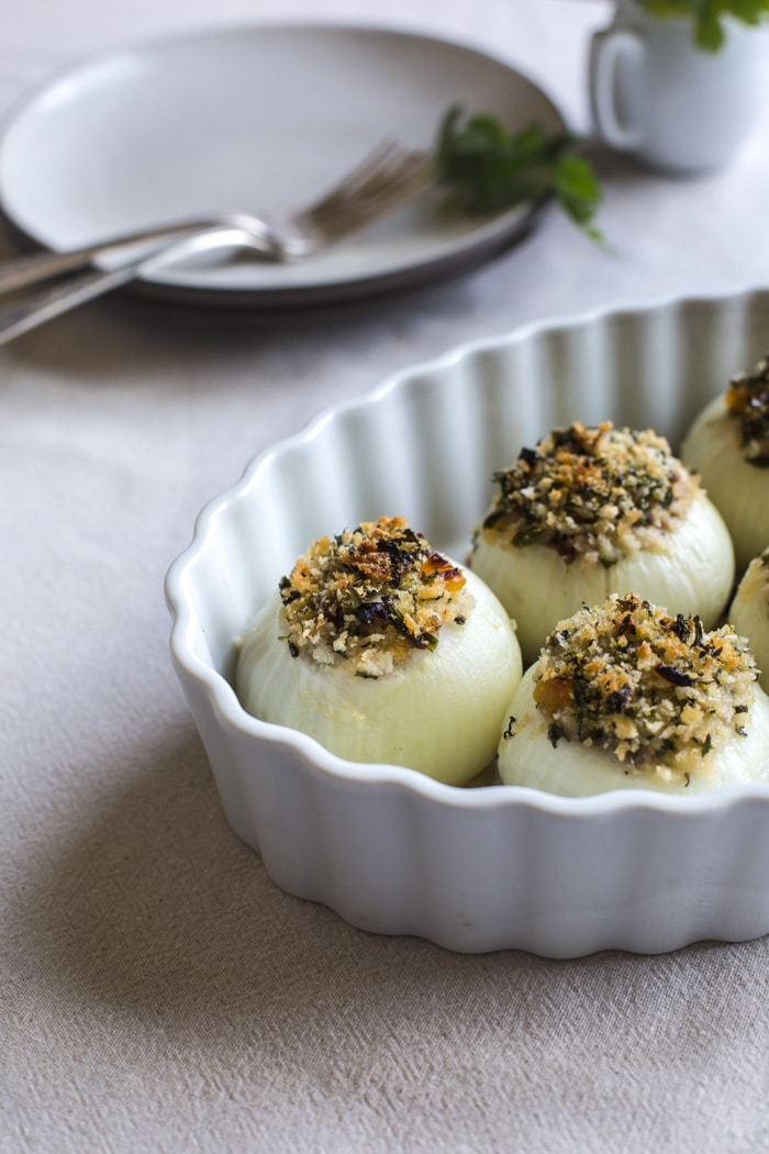 Close up view of Stuffed Baked Onions in a bowl with tableware in the background