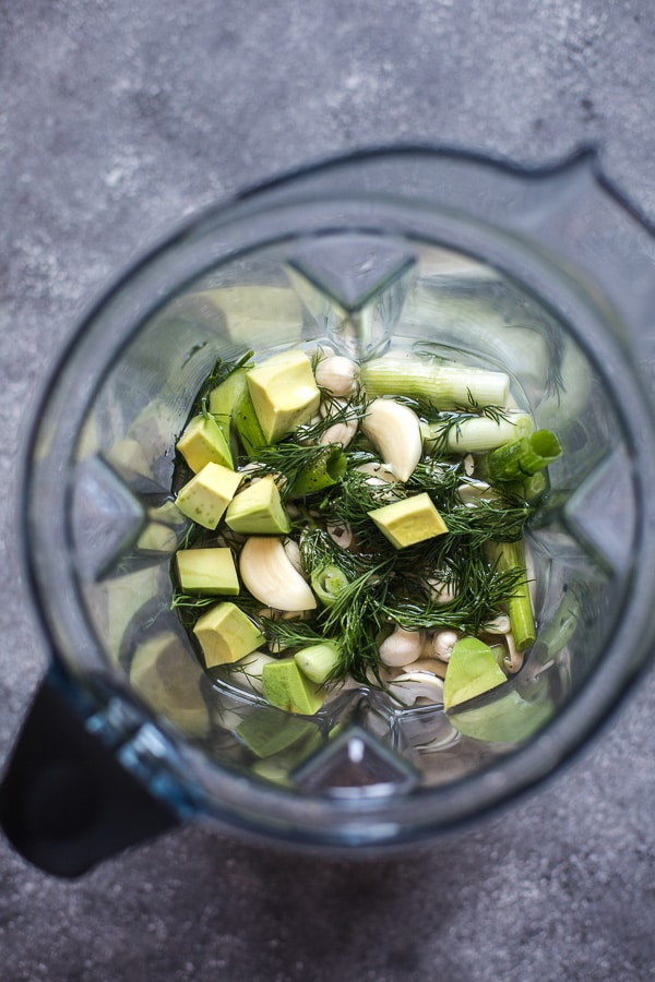 Overhead view of avocado, cashew and herbs in a Vitamix